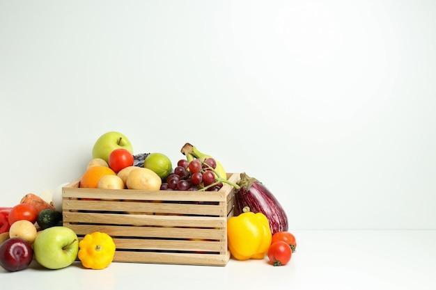 Caja de madera con diferentes verduras y frutas en mesa blanca