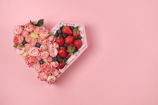 Caja de madera en forma de corazón llena de rosas y fresas maduras sobre un fondo rosa