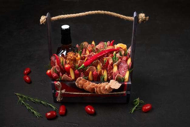 Caja de madera llena de salchichas ahumadas, queso, tomates y una botella de whisky en negro.