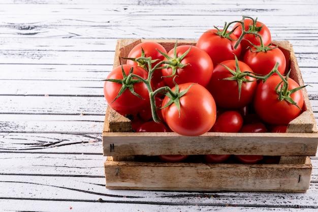 Caja de madera llena de tomates rojos sobre madera blanca