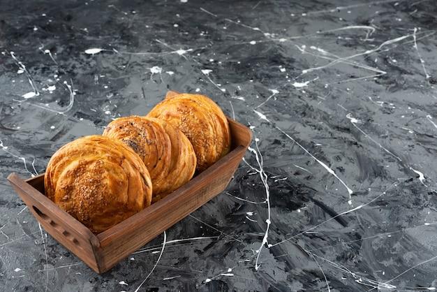 Una caja de madera con pastelería nacional de azerbaiyán sobre un fondo de mármol.