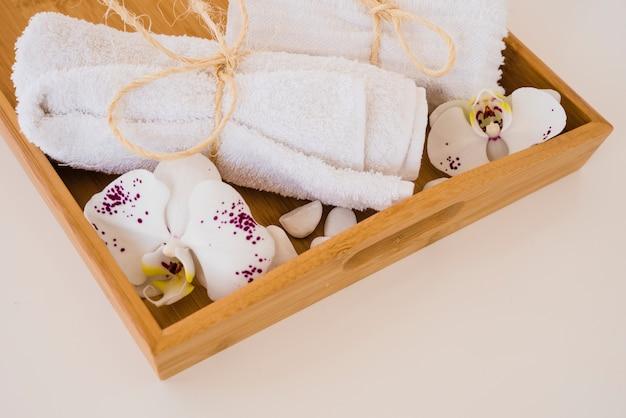 Caja de madera con toallas y flores.
