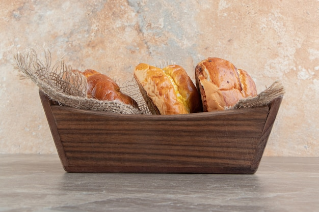 Caja de madera de varios pasteles sabrosos sobre fondo de mármol