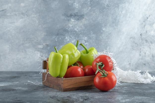 Caja de madera de verduras frescas maduras sobre fondo de mármol