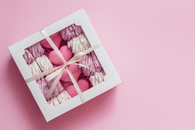 Caja con malvaviscos y macarrones sobre fondo rosa