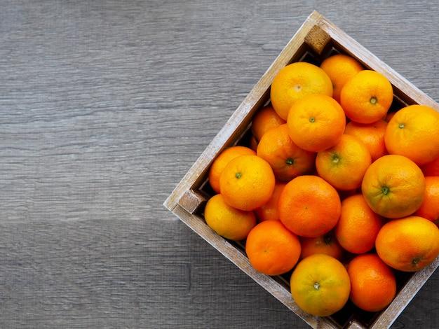 Caja de mandarinas en mesa de madera.