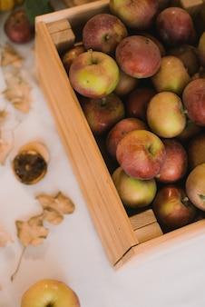 Una caja de manzanas dulces rústicas sobre una mesa en casa. bodegón otoñal.