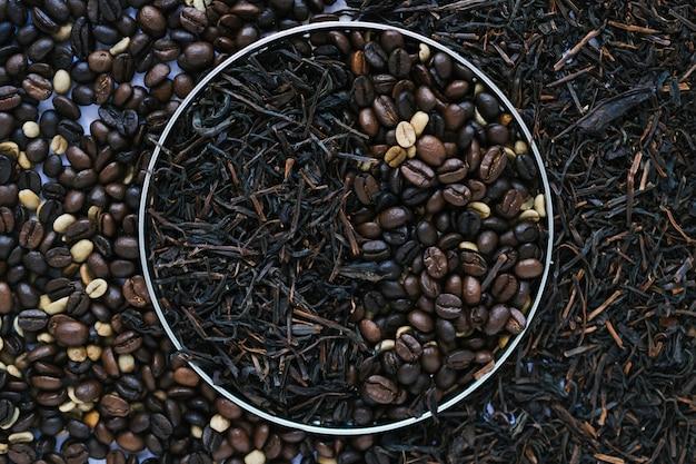 Caja de metal con hojas de té secas y granos de café.