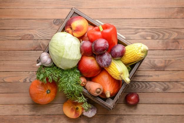 Caja con muchas verduras y frutas saludables en superficie de madera