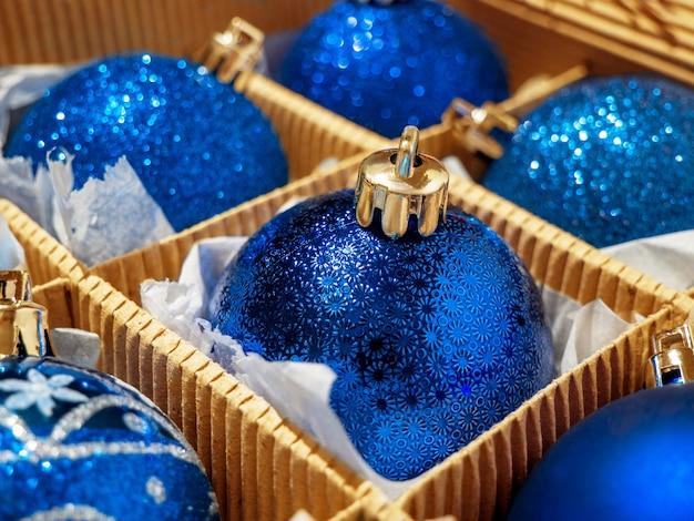 Una caja de navidad con bolas de navidad azules y regalos, baratijas de navidad preparándose para las vacaciones