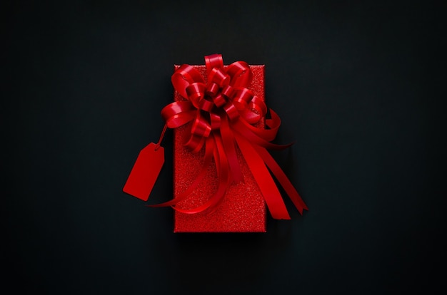 Caja de navidad roja con cinta de lazo rojo y etiqueta de precio en negro