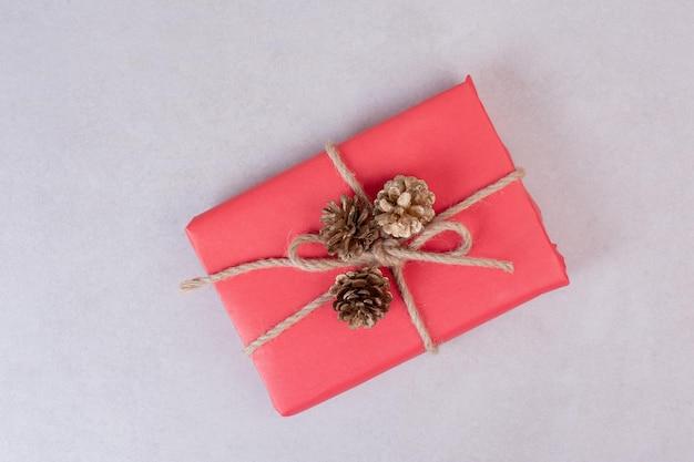 Caja de navidad roja con tres piñas en mesa blanca.