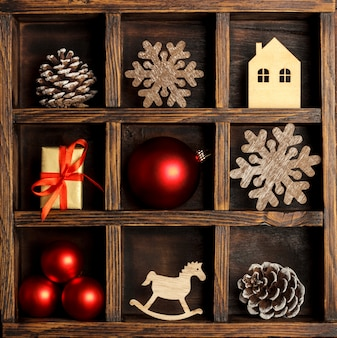Caja navideña de madera con adornos rojos.