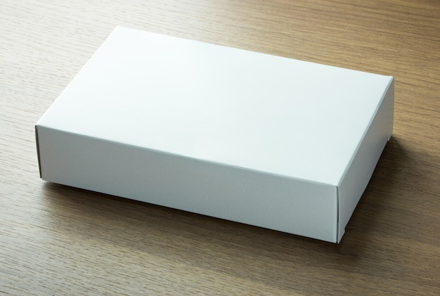 Caja de papel blanco en blanco sobre fondo de madera oscura