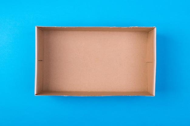 Caja de papel cartón vacía sobre fondo azul.