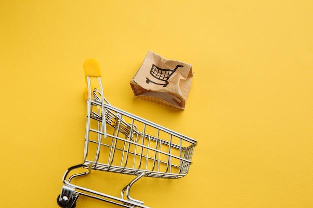 Caja de papel dañada y carro de compras sobre un fondo amarillo. concepto de entrega. accidente de envío.