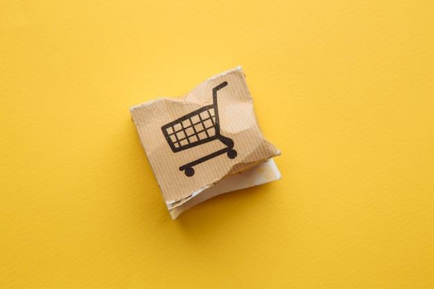 Caja de papel dañada sobre un fondo amarillo. concepto de entrega. accidente de envío.