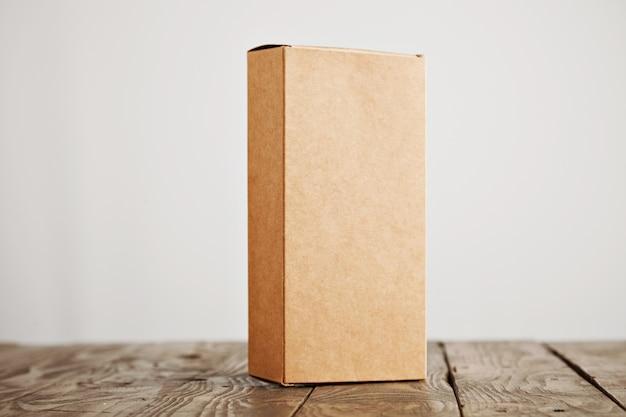 Caja de paquete de cartón artesanal presentada verticalmente sobre una mesa de madera cepillada acentuada, aislada sobre fondo blanco