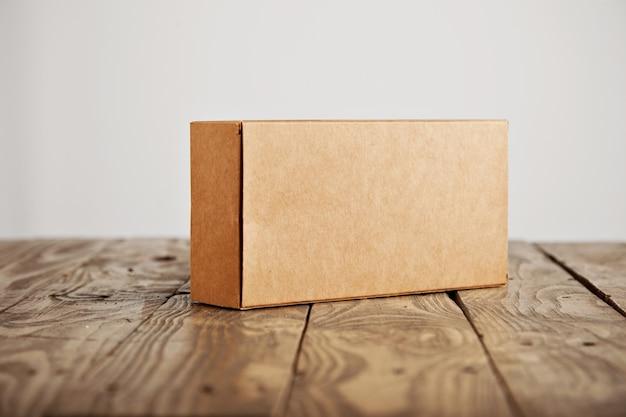 Caja de paquete de cartón sin etiqueta artesanal presentada en mesa de madera cepillada acentuada, aislada sobre fondo blanco