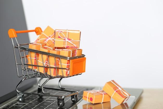 Caja de paquete marrón y modelo de carro de compras en miniatura en el teclado de la computadora