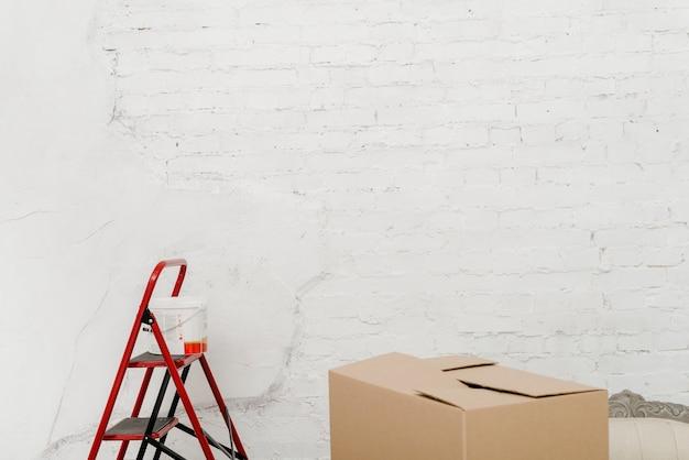 Caja de pintura y cartón cerca de la pared