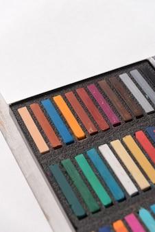 Caja con pintura pastel de colores sobre papel blanco