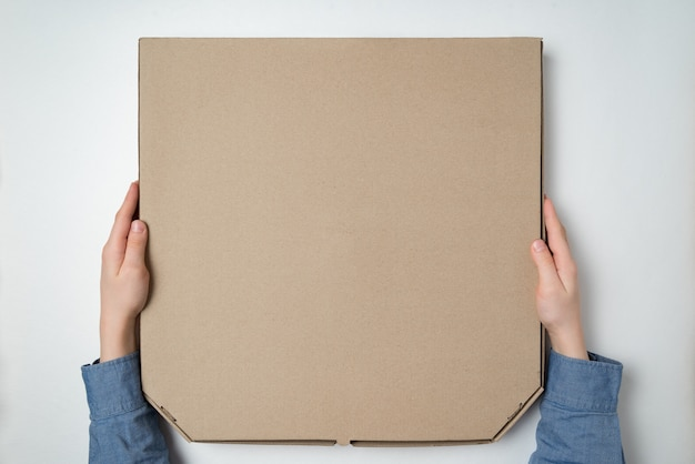 Caja de pizza en manos de los niños en blanco