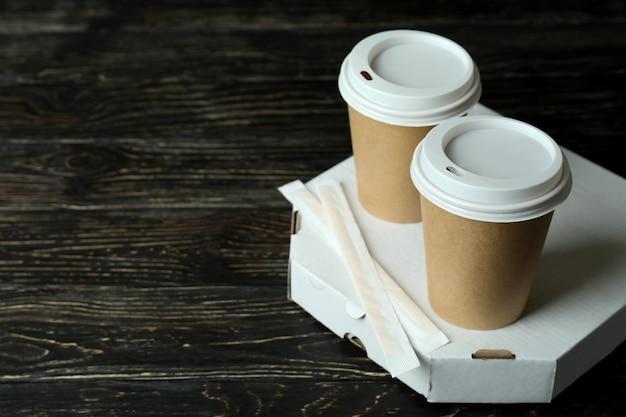 Caja de pizza y vasos de papel en madera