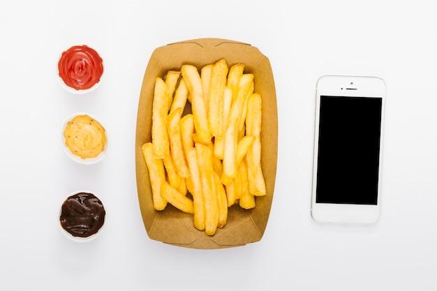 Caja plana de papas fritas con salsas y maqueta de smartphone.
