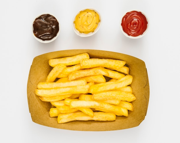 Caja plana de patatas fritas con salsas.