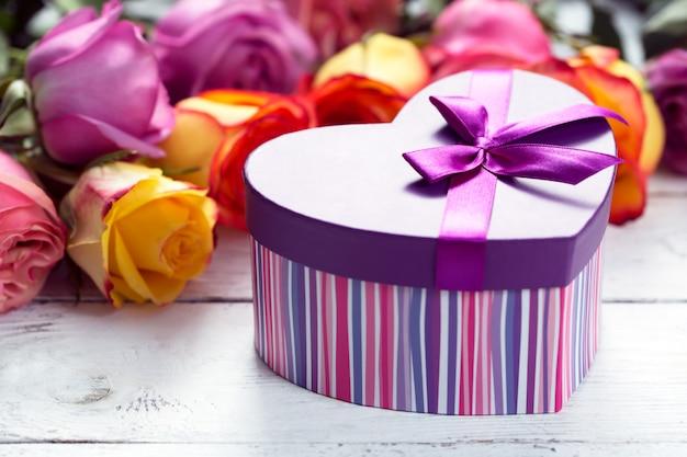 Caja presente en primer plano, rosas moradas y amarillas en la mesa de madera