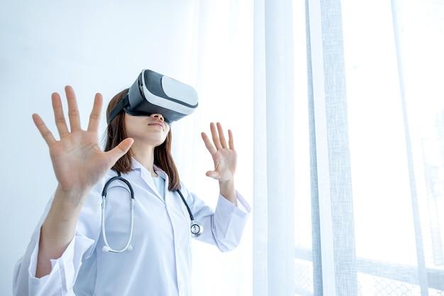Caja de realidad virtual. una joven asiática con uniforme de médico hace una expresión de entusiasmo mientras aprende con la tecnología de realidad virtual.