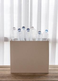 Caja de reciclaje llena de recipientes de plástico transparente.
