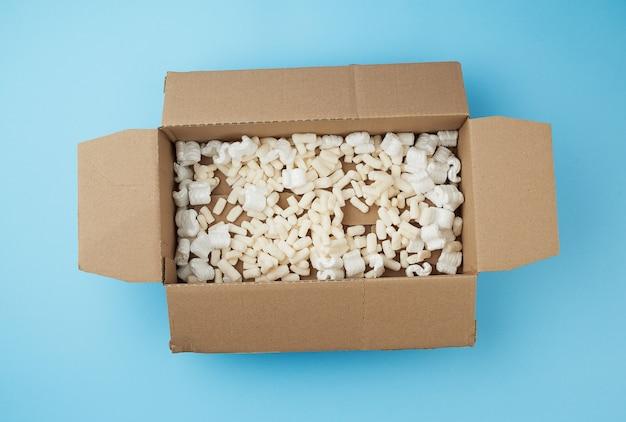 Caja rectangular abierta de cartón marrón con relleno de espuma blanca