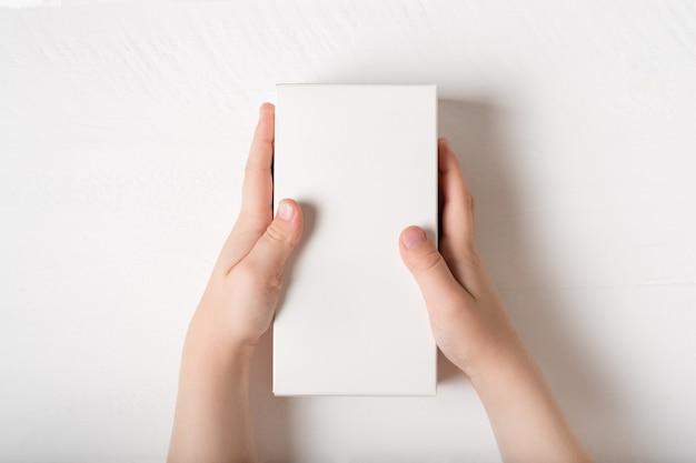 Caja rectangular de cartón blanca en manos de niños.
