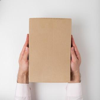 Caja rectangular en manos de hombres. vista superior. marco vertical