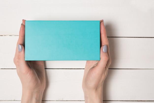 Caja rectangular turquesa en manos femeninas. vista superior. mesa blanca