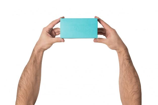 Caja rectangular turquesa en manos masculinas.
