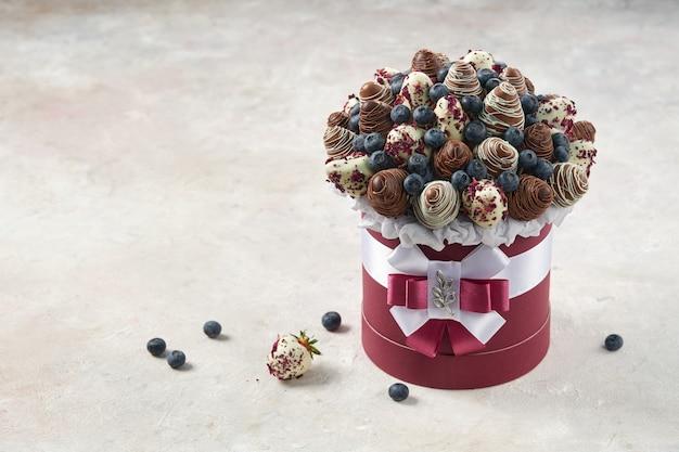 Caja redonda llena de fresas cubiertas de chocolate y arándanos maduros sobre mármol como plantilla para una tarjeta de invitación de cumpleaños