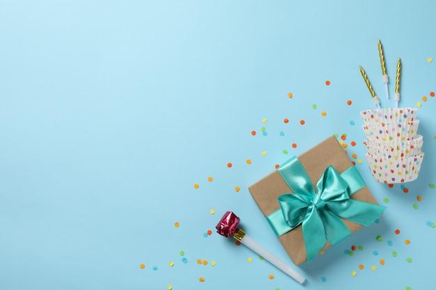 Caja de regalo con accesorios de arco y cumpleaños sobre fondo azul, vista superior