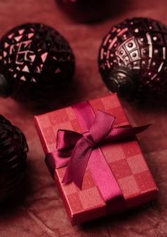 Una caja de regalo con adornos navideños sobre la mesa en tonos rojos y burdeos el concepto de unas vacaciones
