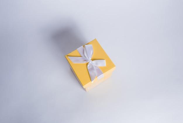 Caja de regalo amarilla con cinta blanca sobre una mesa blanca