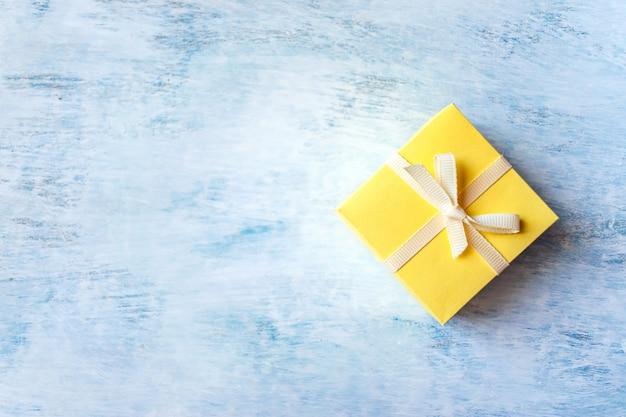 Una caja de regalo amarilla sobre fondo azul claro