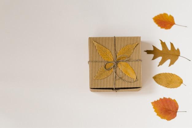 Caja de regalo artesanal, atada con una cuerda con un lazo y hojas caídas de otoño. hojas amarillas y rojas. descuentos de compras en otoño.