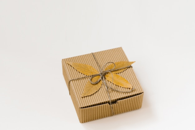 Caja de regalo artesanal, atada con una cuerda con un lazo y hojas caídas de otoño sobre un fondo beige