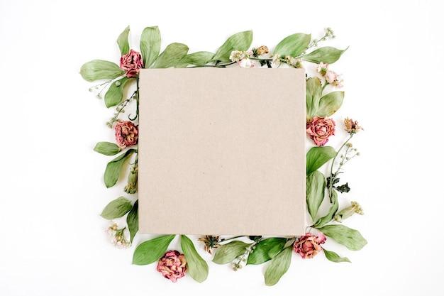 Caja de regalo artesanal y composición floral con rosas rojas y hojas verdes sobre superficie blanca