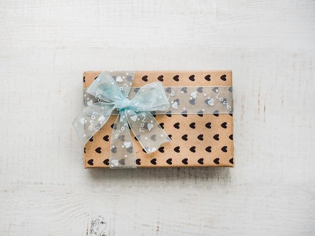 Caja con un regalo, atada con una cinta, nota con palabras dulces