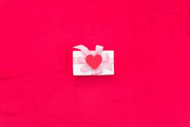 Una caja de regalo atada con cinta de raso de color rojo fondo