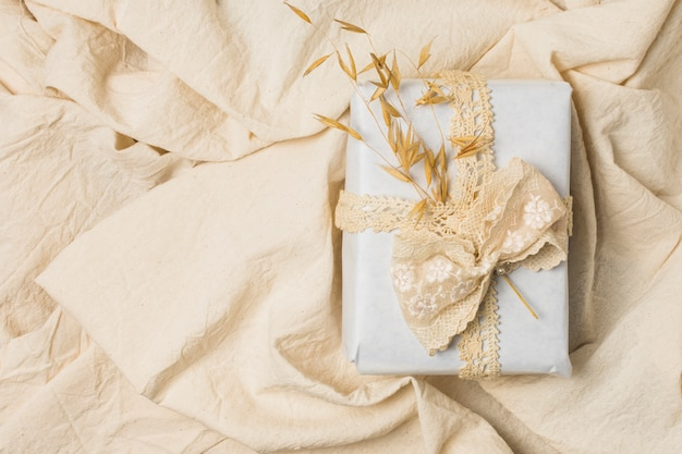 Caja de regalo atada con encaje de diseñador sobre sábana arrugada