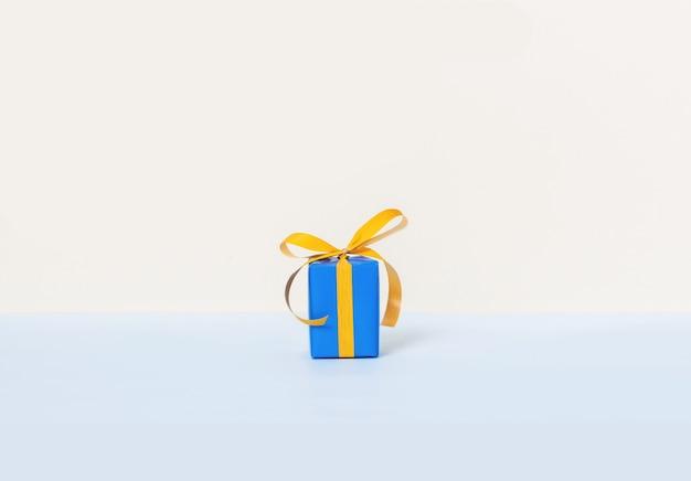 Caja de regalo azul con cinta amarilla sobre un fondo pastel.